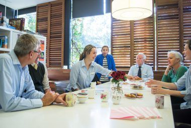 Country Club members drink tea and biscuits around a table